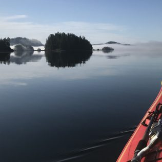Kayak out on the water with views of forested islands